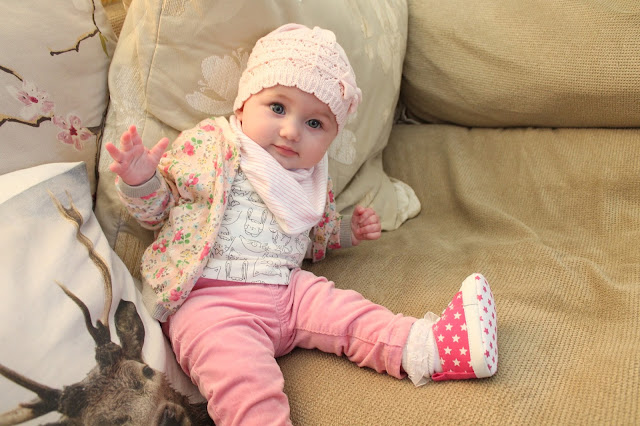 baby girl wearing pink corduroy trousers, star pattern converse, cat print t-shirt, floral cardigan and pink knitted hat