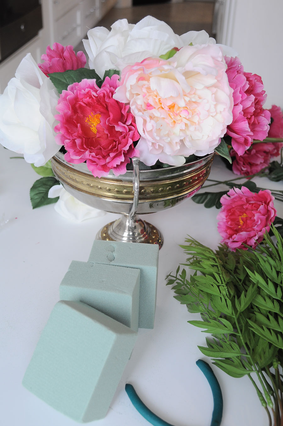 Using fake or faux florals such as peonies can make a floral arrangement look glam and luxe. Here's a DIY tutorial for how to achieve this look yourself.