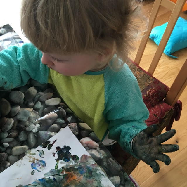 Toddler concentrating and holding hand up covered in murky brown paint