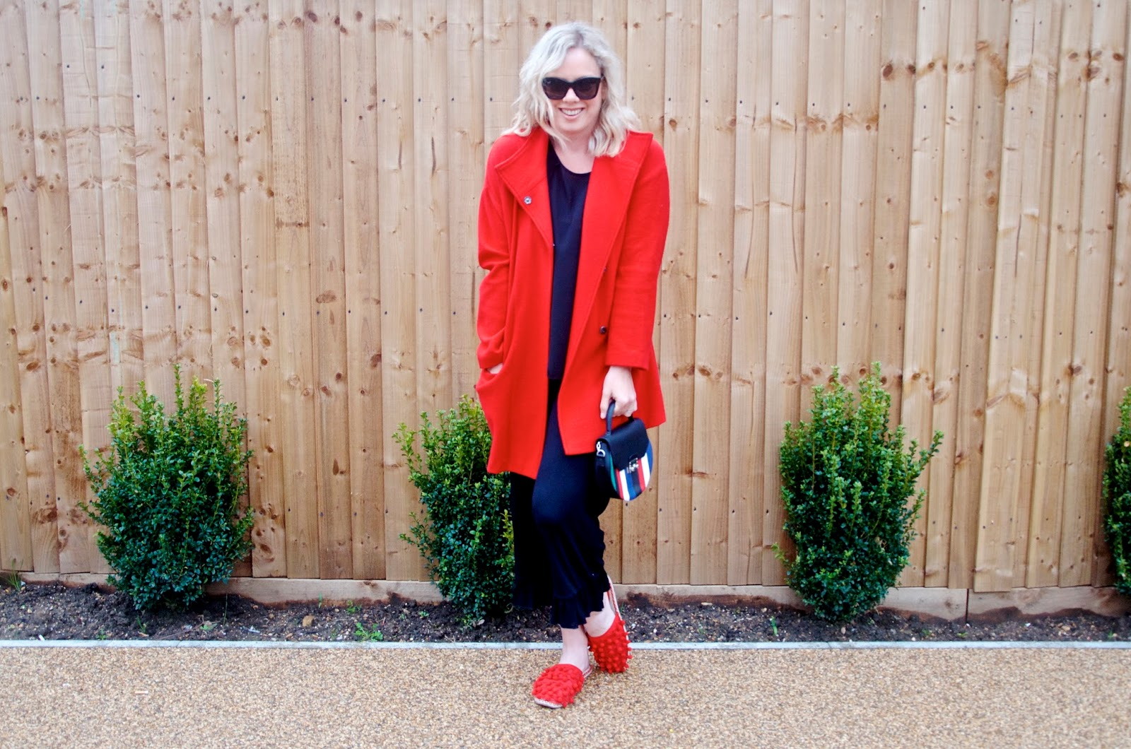 red coat, red shoes, striped bag, green bushes and wooden wall