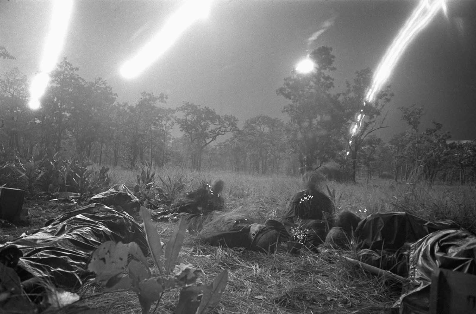 Flares from planes light a field covered with the dead and wounded of the ambushed battalion of the U.S. 1st Cavalry Division in the Ia Drang Valley, Vietnam, on November 18, 1965, during a fierce battle that had been raging for days. Units of the division were battling to hold their lines against what was estimated to be a regiment of North Vietnamese soldiers. Bodies of the slain soldiers were carried to this clearing with their gear to await evacuation by helicopter.
