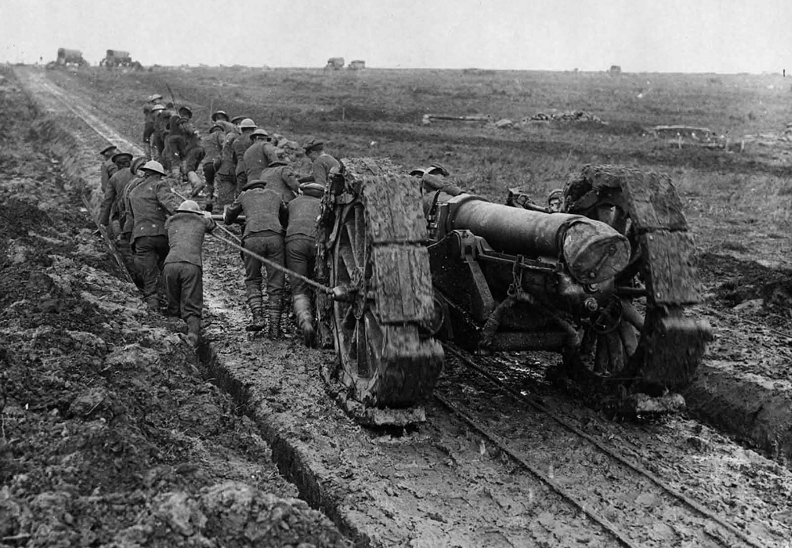 Soldiers struggle to pull a huge piece of artillery through mud. The gun has been placed on a track created for a light railway. The soldiers are pushing a device, attached to the gun, that possibly slots into the tracks. Some of the men are in a ditch that runs alongside the track, the rest are on the track itself. A makeshift caterpillar tread has been fitted to the wheels of the gun, in an attempt to aid its movement through the mud.