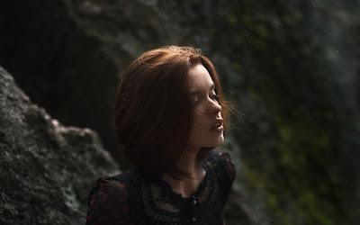 Linda chica apoyada en una roca mirando a la nada