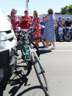 A group of four ladies are standing on the track between the team buses. In the foreground one can see the green bikes of the Bora Hansgrohe team leaning against the front of the bus. In the background are spectators and other bikes leaning on the track barrier fence.