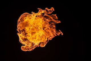 An orange flame with no visible source, set against an entirely black background.