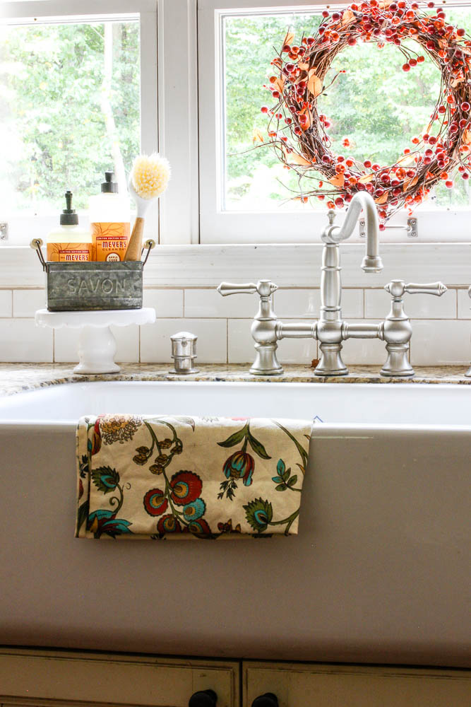 Farmhouse sink in kitchen with bridge faucet and white subway tile backsplash