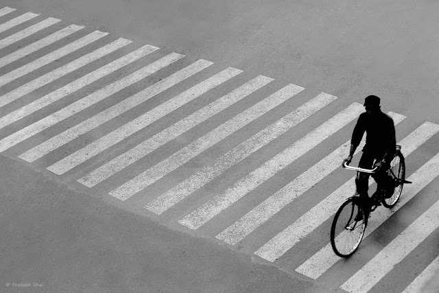 A Man riding a bicycle, passing by the Zebra Crossing at M I Road, Jaipur, India.
