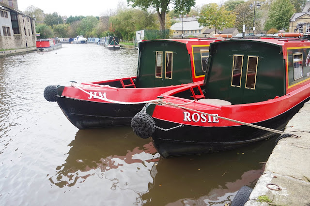 canal boats on the water in skipton. Both have a red trim, one is painted 'Jim' in white, the other 'Rosie'