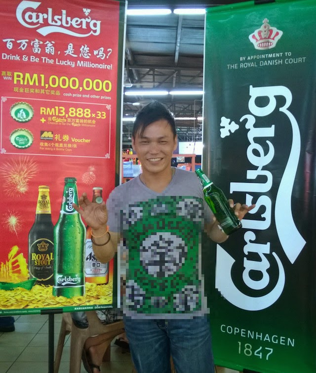 Wong See Min gives us his biggest smile as he displays a large bottle of Carlsberg and the bottle cap which put him in the running to become the 'Carlsberg Millionaire'