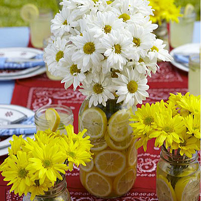 These mason jars lined with fresh lemons and displayed with fresh flowers are cute centerpieces.