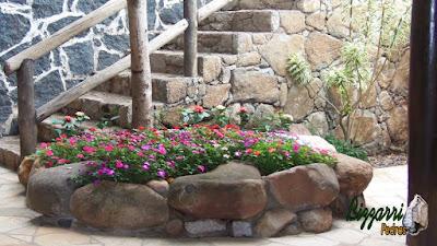 Canteiro com pedras do rio com as paredes de pedra, a escada de pedra e o corrimão de madeira.