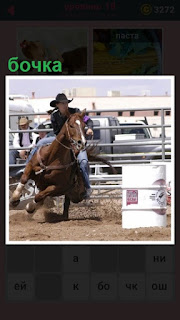 бочка стоит в загоне в котором всадник на лошади скачет