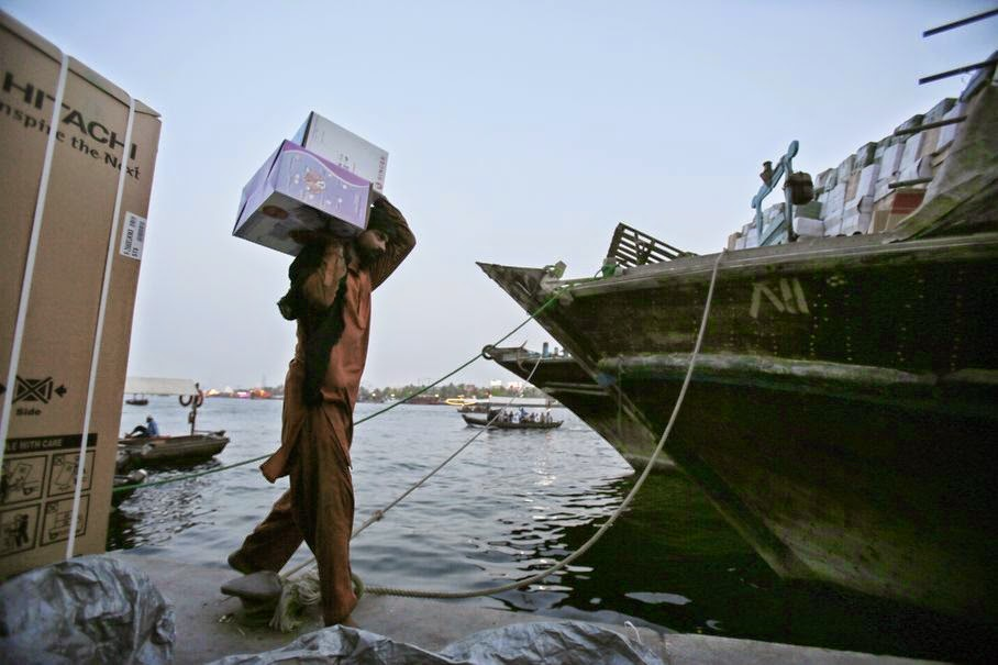 In this Thursday, May 29, 2014 photo, an Asian laborer carries imported goods to a dhow at the creek in Dubai, United Arab Emirates. Beneath a glitzy skyline wooden boats ply Dubai Creek, the historic heart of a city that was transformed in little more than a generation from a tiny pearling and fishing port to a global trading hub.
