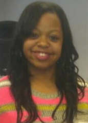 A smiling young Black woman with long, straightened hair, wearing a brightly-colored sweater
