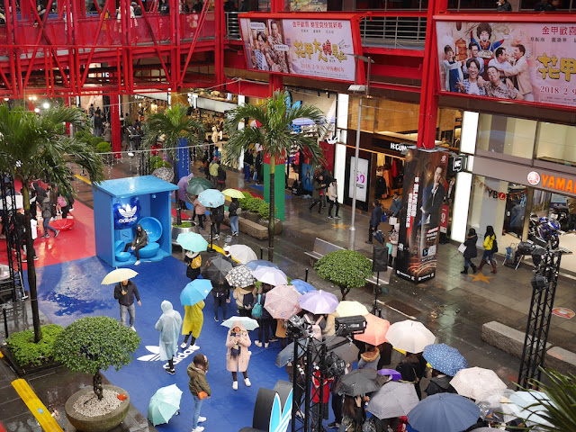 people with umbrellas waiting in line to take photos at an Adidas promotion