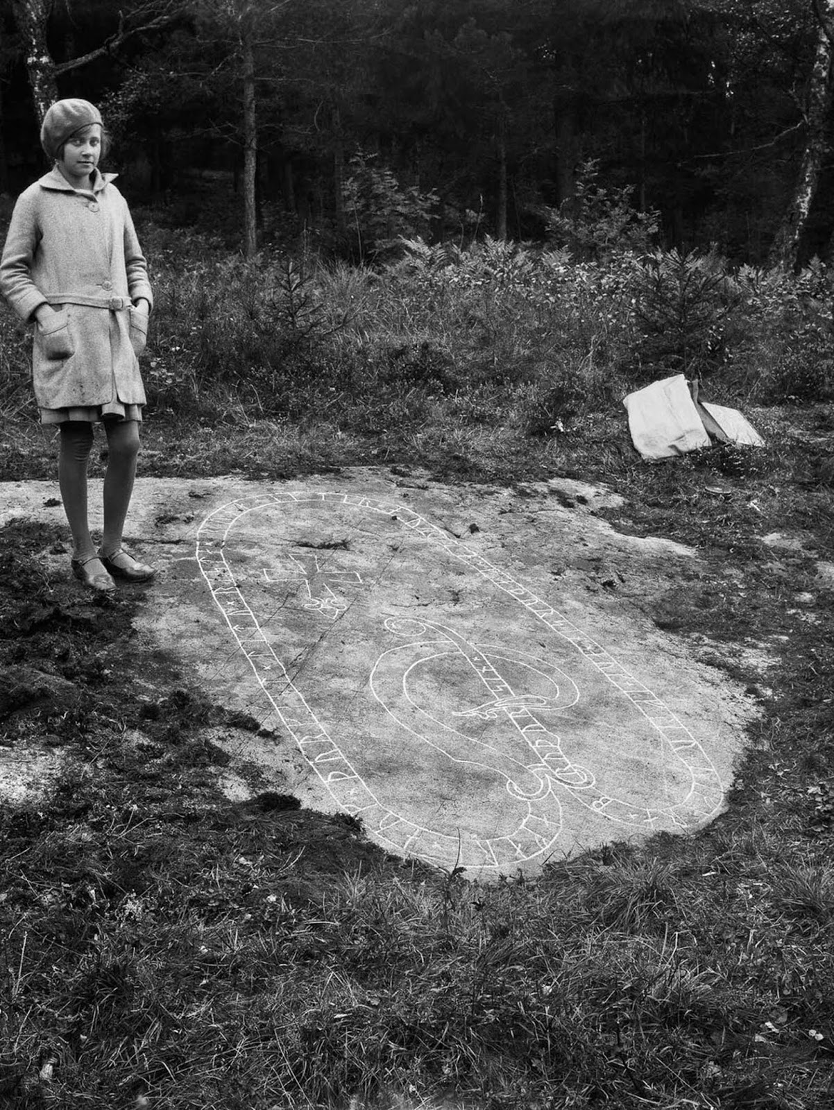 A girl stands at a flat rock with a runic inscription in Skillinge. The inscription reads,