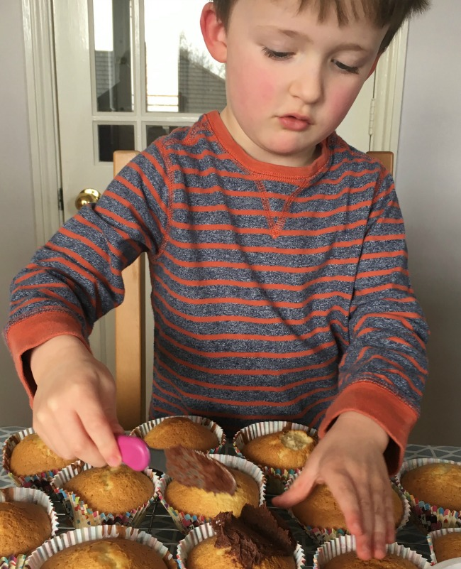 boy-icing-fairy-cakes-one-cake-has-bite-from-top