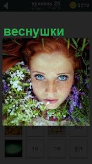 Лицо девушки обрамлено полевыми цветами, на котором большое количество веснушек с яркими голубыми глазами