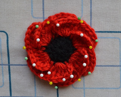 """Hope Bloom"" poppy on ironing board. The red petals are pinned open revealing the black centre."