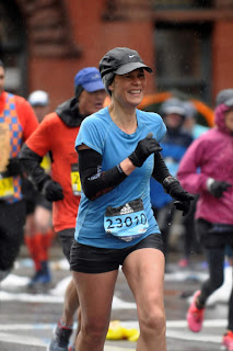 A smiling woman in shorts, long sleeves and gloves, running a long distance race in the rain