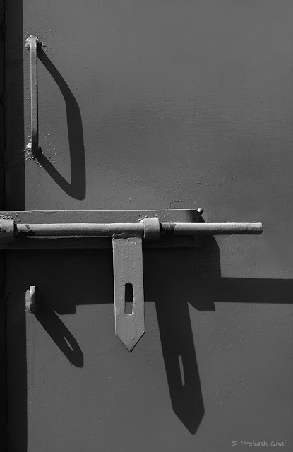 A Minimal Art Photo of Long Shadows of the Handles of a Metal Door in Black and White