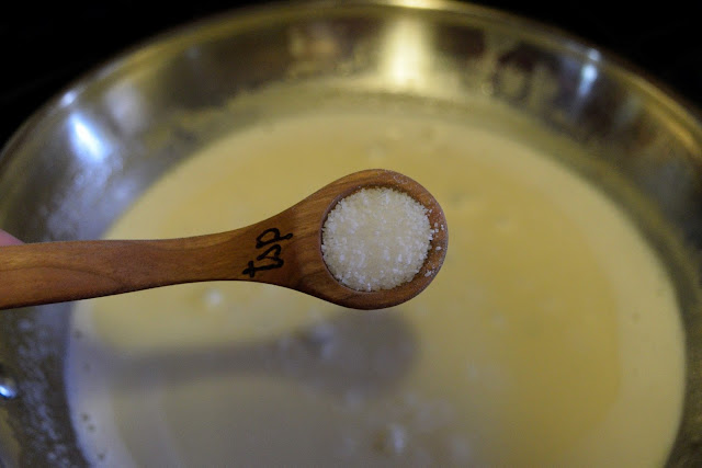 A measuring spoon of salt over the skillet of Marsala sauce.