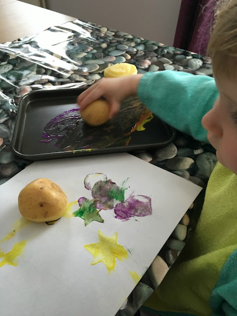 toddlers hand holding potato next to a sheet of paper with potato printing on it
