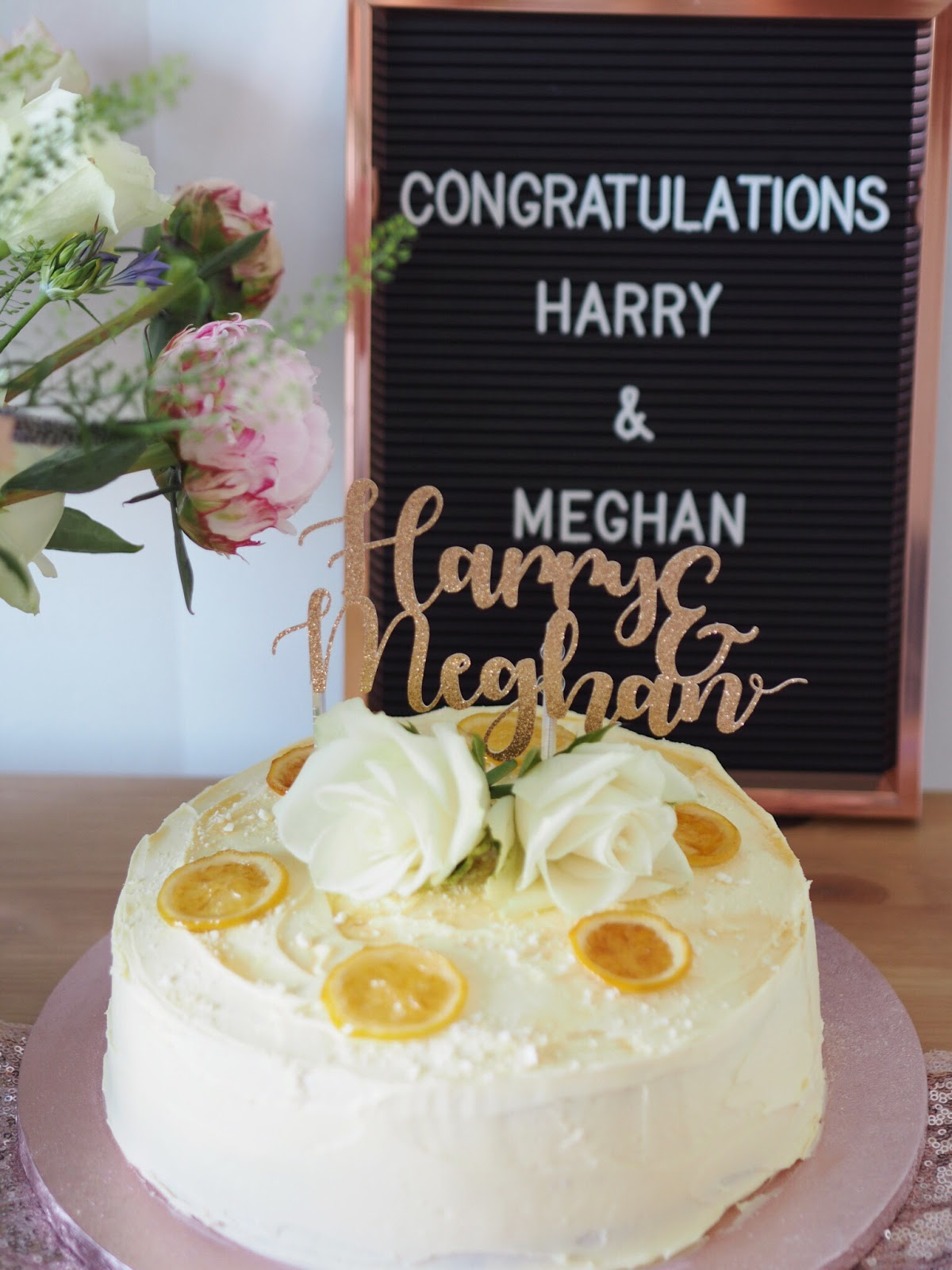 Lemon & Elderflower cake with copper peg board reading congratulations meghan & harry