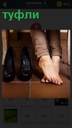 под столом женщина сняла туфли и сидит босиком