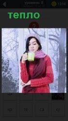 В морозное утро девушка закуталась в шарф, кофту и пьет из чашки теплый напиток согреваясь