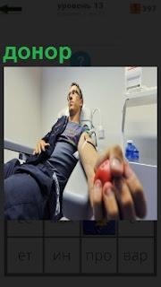 В кресле мужчина донор сдает кровь из вены, качая мячик в ладони