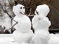 Ağaç dalı kollarıyla birbirlerine kucak açan iki komik kardan adam