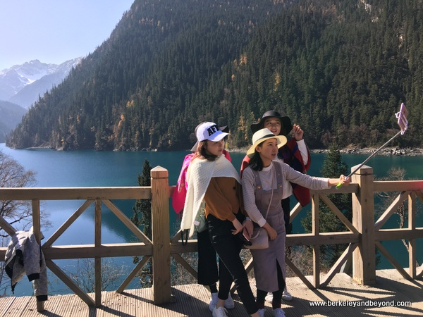 girls take selfie at Long Lake in Jiuzhaigou Valley National Park in Sichuan Province, China