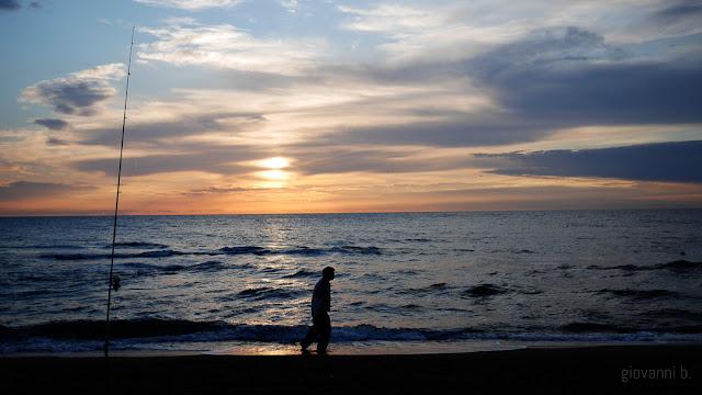 Pescatore sulla spiaggia al tramonto