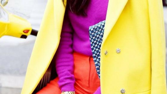 Imagem ilustrativa de um look com casaco amarelo, camisola roxa e calças laranja