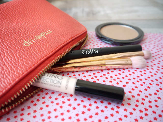 a red makeuo bag with concealer, rose gold brushes, and mascara coming out of it