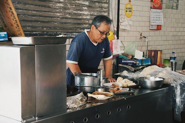 一旁的工作台正現擀著蛋餅皮,準備下鍋油炸。