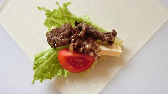 春巻きの皮にリーフレタス、トマト、チーズと一緒に牛肉をのせて包む