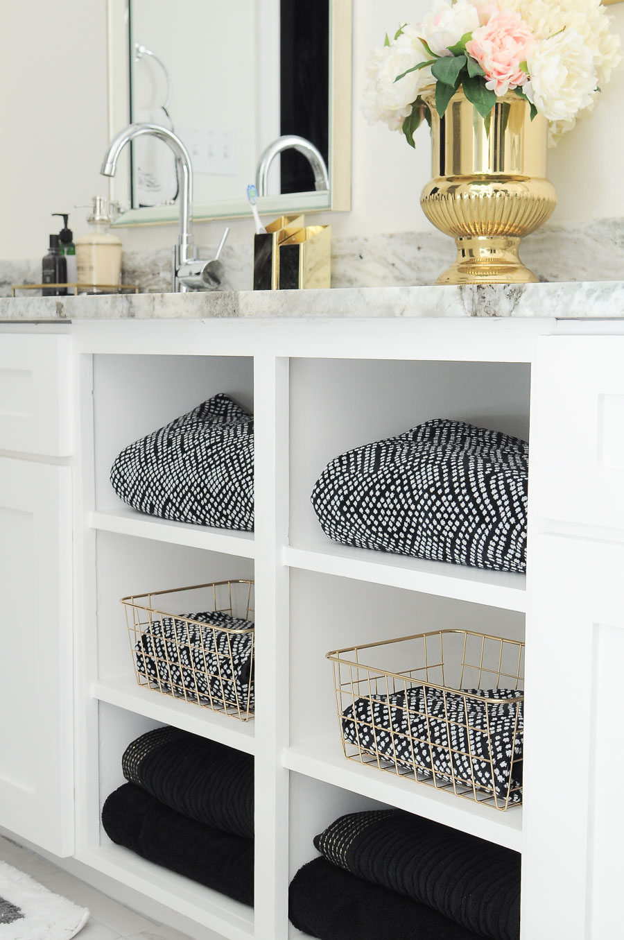Black and white towels paired with gold baskets look gorgeous on the open shelves of this master bathroom vanity. The whole space is just gorgeous!