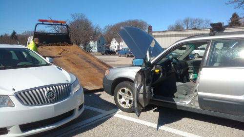 car being loaded onto a flatbed tow truck