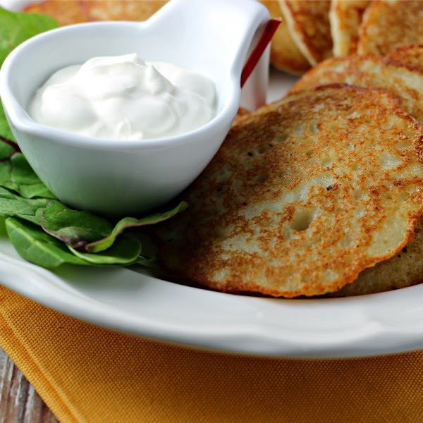 Easy Potato Pancakes by Renee's Kitchen Adventures on a white plate with a lettuce garnish and sour cream