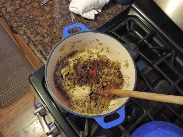 All of the spices being added to the pot.