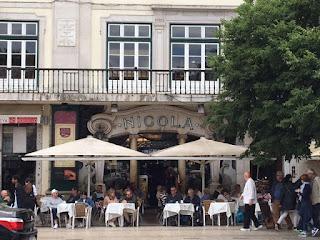 área externa do café Nicola com ombrelones na esplanada, cheia de pessoas