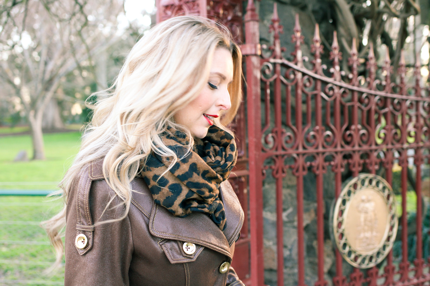 Goldfields Girl wearing leopard print scarf, brown gold trench and black wedge heels