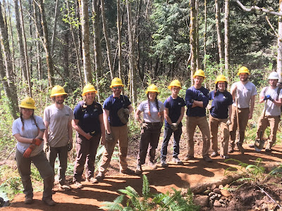 Ten AmeriCorps members line up along a freshly constructed section of trail they completed in Harry-Osborne State Forest.