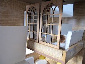 Two one-twelfth scale wooden laser-cut church windows leaning on the top of a modern doll's house mezzanine wall.