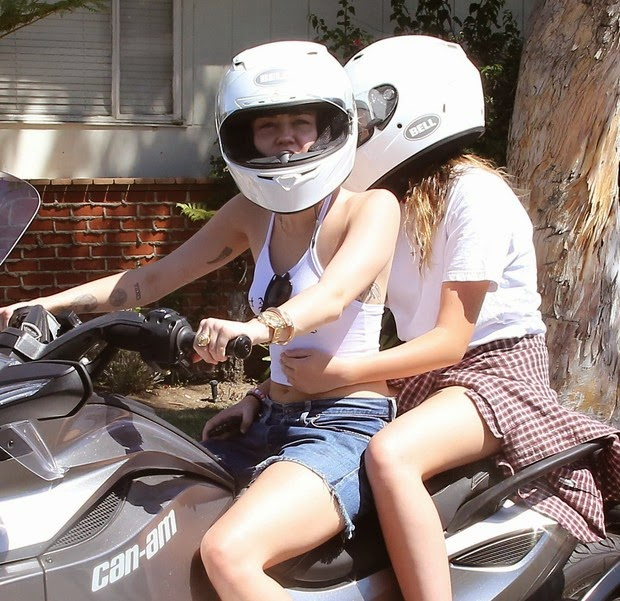 Miley Cyrus rides a motorcycle with his sister