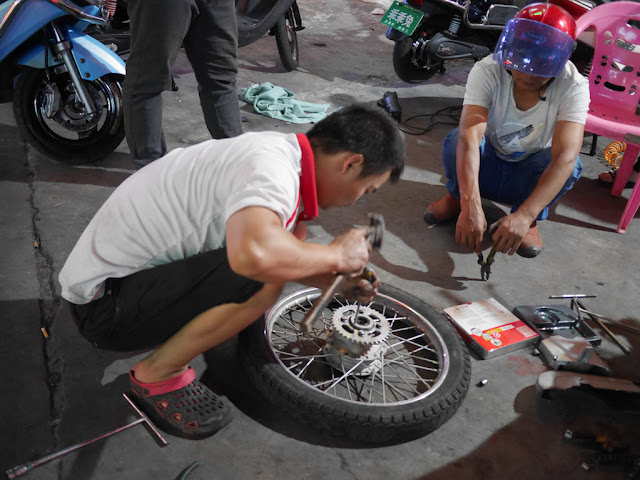 man fixing a motorcycle wheel