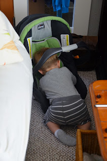 toddler playing with baby car seat