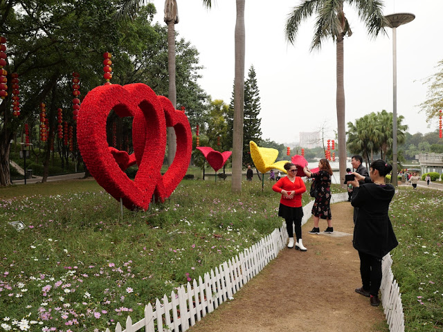 woman posing for photo in front of heart-shaped flower sculptures